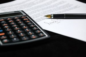 A calculator next to a signed document.