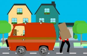 A mover putting cardboard boxes into a moving van.