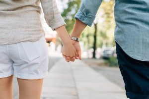 The couple, holding hands.