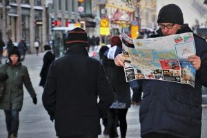 A man reading some papers carefully on the street.