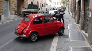 Small red Fiat badly parked.