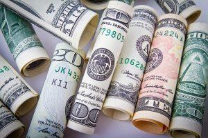 Different amount dollar bills rolled up.