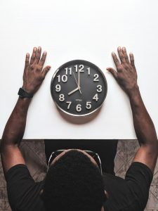 Man looking at a clock located on a table.