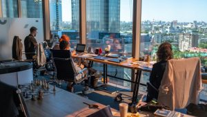 A group of people sitting at a large office desk while enjoying a beautiful view.