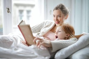 A mother and daughter reading a book.