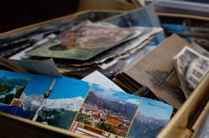 A lot of postcards in a cardboard box.
