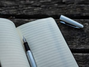 an image of a grey and black pen on top of a note book