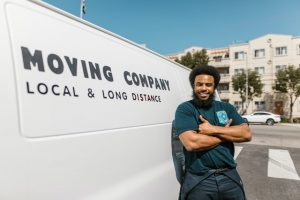 A man leaned back on a moving van symbolizing the necessity for hiring movers when moving a production line