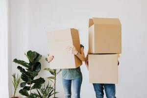 Two people holding moving boxes